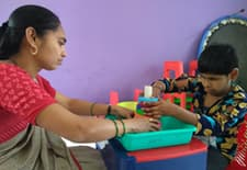 Child with deafblindness engaged in stacking tower activity with the support of her special educator